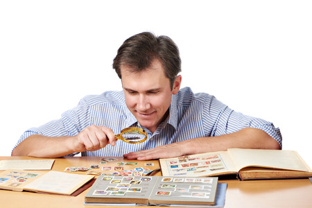 고립 된 돋보기와 우표의 컬렉션을보고하는 남자 스톡 콘텐츠
