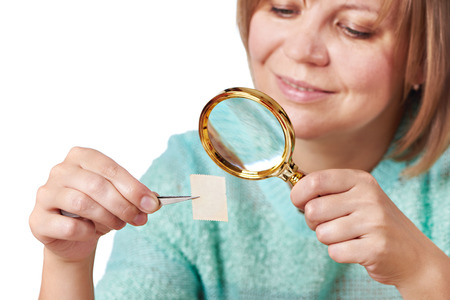 postage stamps: Woman watching postage stamps close-up isolated