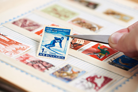 Postage stamp with skier on album close-up
