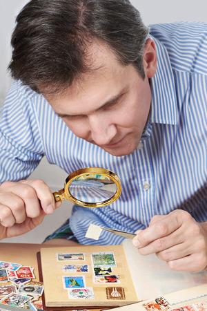Человек смотрит коллекцию почтовых марок, изолированных