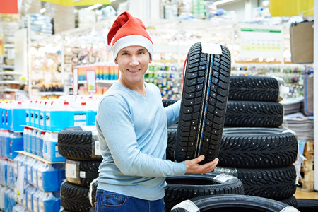 Happy man in Santa hat with a gift winter tires in store Christmas sales Stock Photo