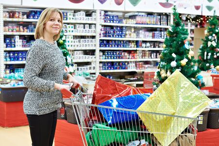 woman shopping cart: Beautiful woman with shopping cart in a supermarket at the Christmas sale
