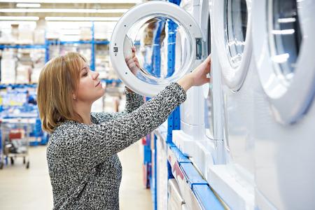 Женщина домохозяйка выбирает стиральную машину в магазине бытовой техники