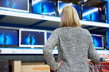 televisor: Woman looks at LCD TVs in supermarket