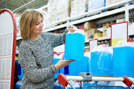 antifreeze: Woman buys nonfreezing liquid in the supermarket Stock Photo