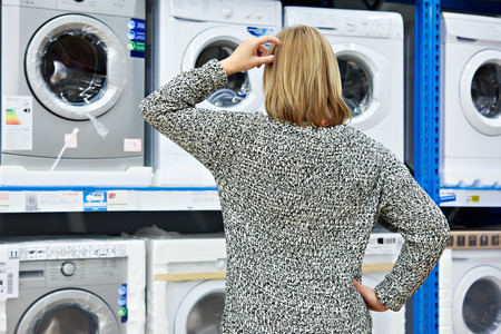 appliances: Woman chooses washing machine in the shop of home appliances Stock Photo
