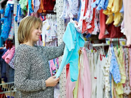 chooses: Beautiful woman chooses child rompers in store Stock Photo