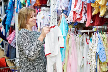Красивая женщина выбирает ребенка в магазине детский комбинезон