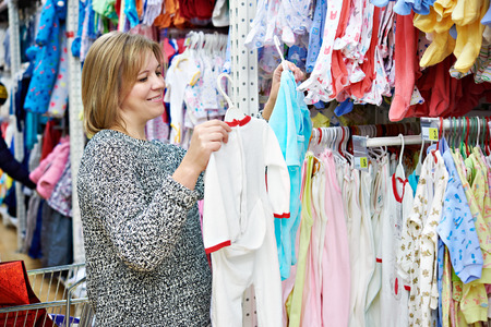 Beautiful woman chooses child rompers in store Фото со стока