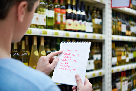 wine trade: Man chooses bottle of wine for date in the store Stock Photo