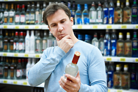 vodka: Man chooses bottle of vodka in the store
