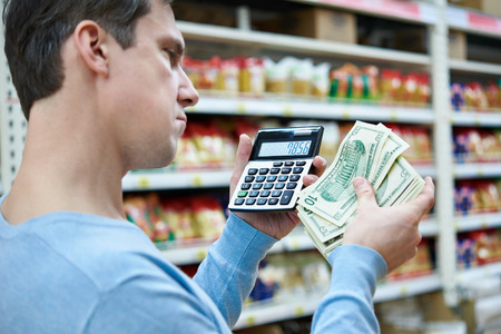 considers: Man with dollars and calculator considers costs in the store Stock Photo