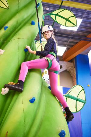artifical: Girl climbing to amusement park on artifical green tree