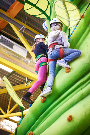 artifical: Two girls climbing to amusement park on artifical green tree