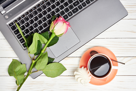 Office desk table with laptop, rose and coffee cup