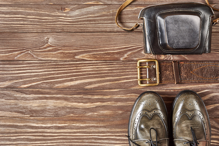 suede belt: Green leather shoes and retro still camera on wooden background Stock Photo