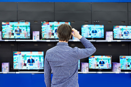 produce departments: Man looks at LCD TVs in supermarket