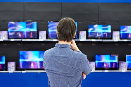 televisor: Man looks at LCD TVs in supermarket