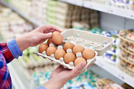 В руках женщины упаковки яйца в супермаркете