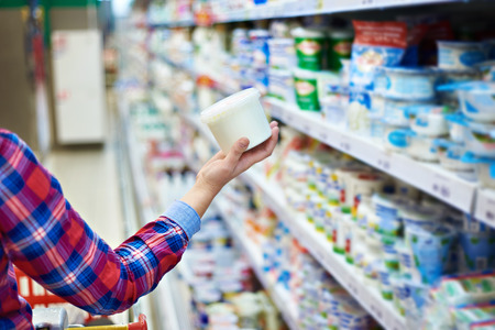 Woman shopping sour cream in grocery store