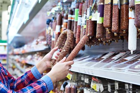 smoked sausage: Woman chooses smoked sausage in the store Stock Photo