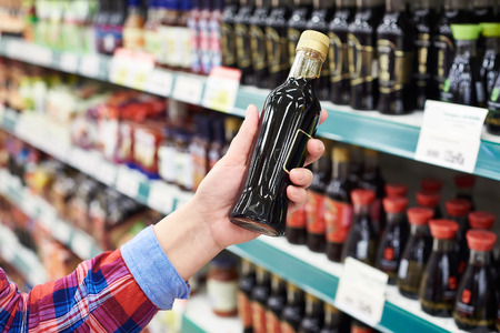 buyer: Buyer with the soy sauce in a store