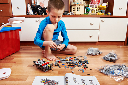 constructor: Little boy collects plastic constructor on wooden floor