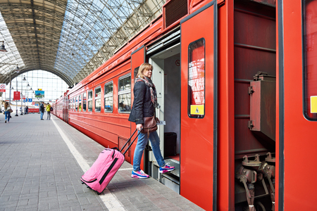 holiday maker: Woman tourist with suitcase sits on the train at the railway station