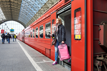 holiday maker: Woman tourist with a suitcase coming out of the train at the station