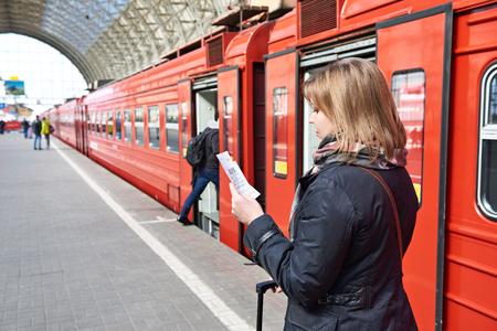 Femme près du train vérifie son billet à la plate-forme de la gare