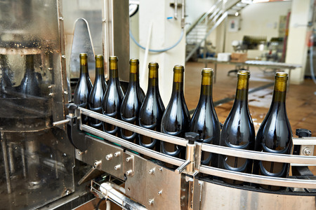Bottling and sealing conveyor line at winery factory Фото со стока