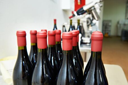 sealing: Bottles of wine in the factory after sealing with paraffin Stock Photo