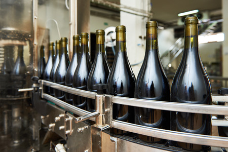 Bottling and sealing conveyor line at winery factory Banco de Imagens