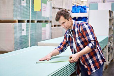 misure Uomo con fogli roulette del muro a secco nei materiali da costruzione negozio