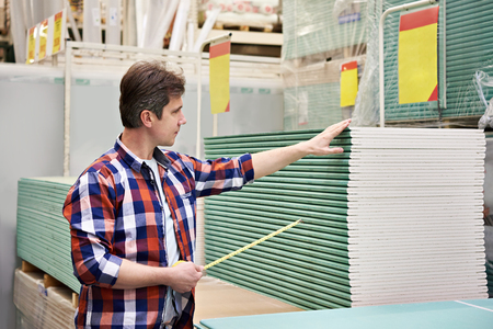 drywall: Man measures with roulette drywall sheets in the store building materials