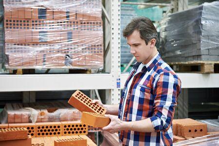 materiales de construccion: El hombre elige un ladrillo de construcción en la tienda