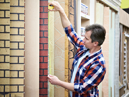 measures: Man measures with roulette decorative panel in hardware store Stock Photo