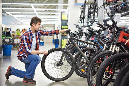 Человек проверяет велосипед перед покупкой в спортивном магазине