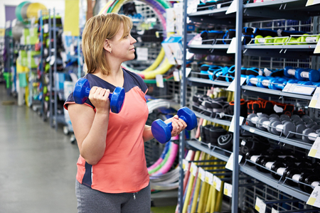 chooses: Woman chooses dumbbells for fitness in the sports shop Stock Photo