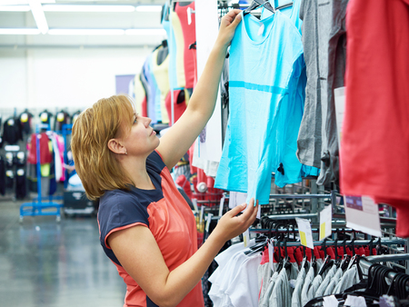 chooses: Woman chooses sportwear for fitness in the sports shop