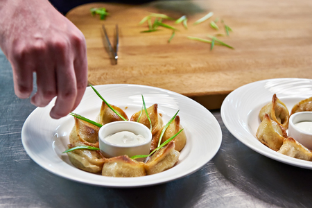 green onions: Cook puts green onions for serving dishes of fried dumplings