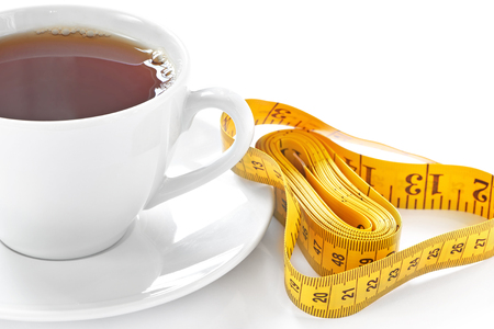 Cup of hot tea with tape measure on white background