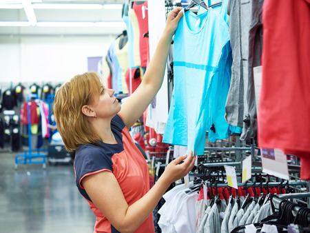 Woman chooses sportwear for fitness in the sports shop
