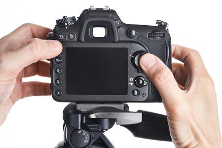 Hands photographer adjust SLR camera isolated on white