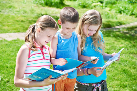 family with one child: Friends reading books outdoors on nature in summer day Stock Photo