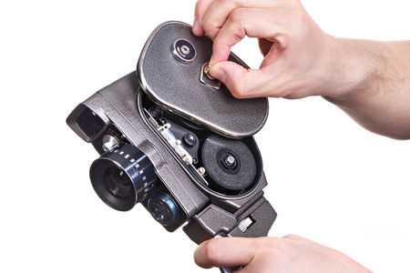 16mm: Retro mechanical hobbies movie camera in the hands of the operator opening cover isolated white