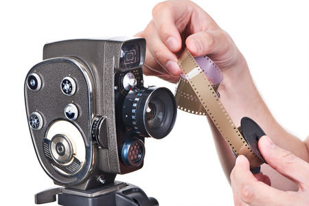 16mm: Retro mechanical movie camera and film in hands operator isolated Stock Photo