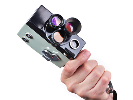 Retro mechanical hobbies movie camera in the hands of the operator isolated white Stock Photo