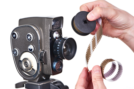 16mm: Retro mechanical hobbies movie camera and film strip in the hands of the operator Stock Photo
