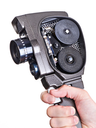 Retro mechanical hobbies movie camera in the hands of the operator with the cover open isolated white